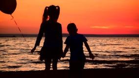 Twee kinderen met een ballon zijn op het strand stock video