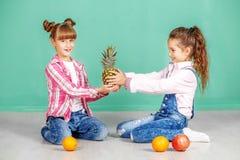 Twee kinderen met fruit, sinaasappel, ananas en granaatappel Sist Royalty-vrije Stock Foto