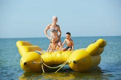Twee kinderen met mamma op de rubberboot die op zee in de zomer varen stock afbeelding