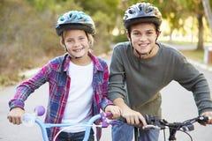 Twee Kinderen op Cyclus berijden in Platteland stock fotografie