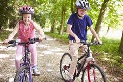 Twee Kinderen op Cyclus berijden in Platteland stock foto's