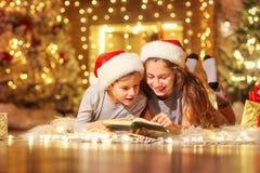 Twee kinderen op de vloer lezen een boek in een ruimte met Kerstmis Stock Foto's