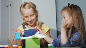 Twee kinderen schilderen samen een model van een somet met waterverf Lessen voor de ontwikkeling van kinderen` s opties stock video