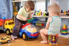Twee kinderen in speelkamer Stock Afbeeldingen