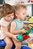 Twee kinderen in speelkamer op stuk speelgoed autoped royalty-vrije stock fotografie