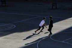 Twee kinderen spelen basketbal op een straatsportterrein stock foto's