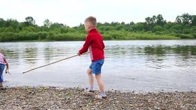 Twee kinderen spelen op de rivierbank Werp stenen, maak plonsen van water Mooi de zomerlandschap stock footage