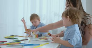 Twee kinderen van jongens en moeder zijn met creatieve ontwikkeling bezig doend thuiswerk door vingertechniek op papier E stock video