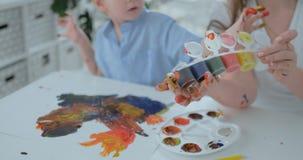 Twee kinderen van jongens en moeder zijn met creatieve ontwikkeling bezig doend thuiswerk door vingertechniek op papier E stock videobeelden