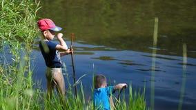 Twee kinderen vangen vissen met hengels op de rivierbank Mooi de zomerlandschap Openlucht recreatie stock videobeelden