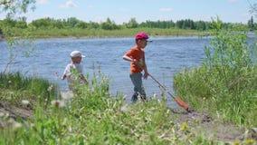 Twee kinderen vangen vissen op de rivierbank Mooi de zomerlandschap Openlucht recreatie stock footage