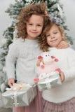 Twee kindmeisjes met giften dichtbij Kerstmisboom Royalty-vrije Stock Afbeeldingen