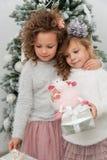 Twee kindmeisjes met giften en schapenstuk speelgoed dichtbij Kerstmisboom Royalty-vrije Stock Fotografie