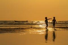 Twee kindschaduwen op het strand met gouden lichte zonsondergang stock afbeeldingen