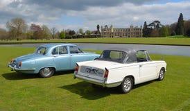 Twee Klassieke auto's voor waardig huis, Triumph Herald Convertible en Jaguar stock afbeelding