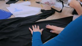 Twee kleermakers die met nieuwe kleermakerijeninzameling werken stock video