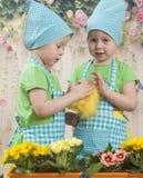 Twee klein aanbiddelijk meisjesspel met gele kuikens Stock Afbeelding