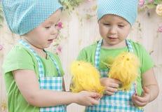 Twee klein aanbiddelijk meisjesspel met gele kuikens Stock Afbeeldingen