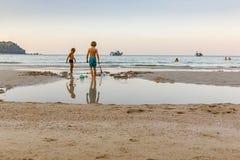 Twee klein jongensspel in het zand op een Thais strand Stock Afbeelding