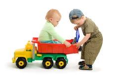 Twee klein jongensspel met stuk speelgoed vrachtwagen Royalty-vrije Stock Afbeeldingen