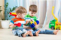 Twee klein jongensspel samen met onderwijsspeelgoed Stock Foto's