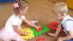 Twee klein kinderenspel met een groot zacht raadsel stock video