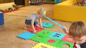 Twee klein kinderenspel met groot zacht raadsel stock videobeelden