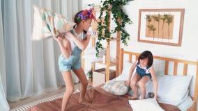 Twee klein leuk meisjesspel op bed, hoofdkussen het vechten, langzame motie stock footage
