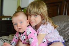 Twee kleine aanbiddelijke Kaukasische zusters zitten samen De kleine zuster koestert haar baby-zuster De meisjes glimlachen en ge stock afbeeldingen