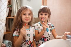 Twee kleine aardige zusters gekleed in identieke overhemden borstelen hun tanden in de badkamers royalty-vrije stock foto's