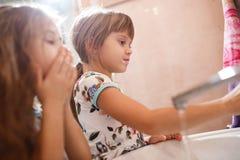Twee kleine aardige zusters gekleed in identieke overhemden borstelen hun tanden in de badkamers royalty-vrije stock afbeeldingen