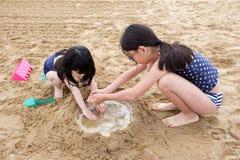 Twee kleine Aziatische meisjes die zand spelen bij strand royalty-vrije stock foto's