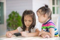 Twee kleine Aziatische meisjeszitting op stoel die celtelefoon met behulp van Royalty-vrije Stock Afbeeldingen
