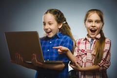 Twee kleine benieuwd zijnde meisjes die laptop geïsoleerde grijze achtergrond gebruiken stock afbeelding