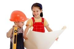 Twee kleine bouwers die met blauwdruk plannen Royalty-vrije Stock Fotografie