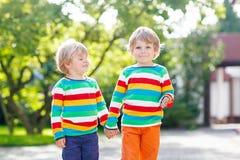 Twee kleine broerskinderen in kleurrijke kleding het lopen hand i Stock Fotografie