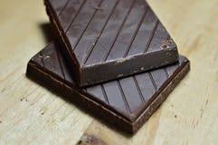 Twee kleine chocoladerepen onder houten raad stock foto