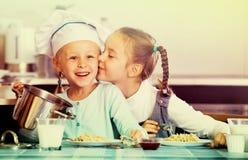 Twee kleine gelukkige meisjes die gezond havermeel eten stock foto