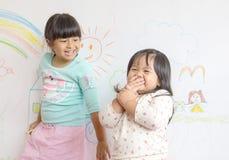 twee kleine glimlachende kinderen in trekken op de muur stock foto's