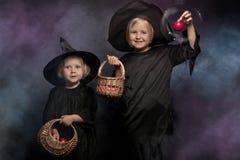 Twee kleine Halloween-heksen, kleurrijke rook op de achtergrond Stock Foto