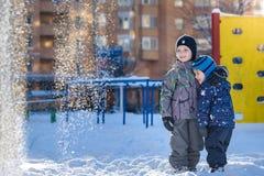 Twee kleine jong geitjejongens die in kleurrijke kleren in openlucht tijdens sneeuwval spelen Actieve vrije tijd met kinderen in  Royalty-vrije Stock Afbeelding