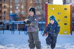 Twee kleine jong geitjejongens die in kleurrijke kleren in openlucht tijdens sneeuwval spelen Actieve vrije tijd met kinderen in  Royalty-vrije Stock Foto