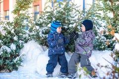Twee kleine jong geitjejongens die in kleurrijke kleren in openlucht tijdens sneeuwval spelen Actieve vrije tijd met kinderen in  Stock Afbeelding