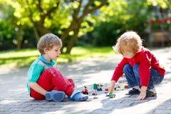 Twee kleine jong geitjejongens die met autospeelgoed spelen Stock Fotografie