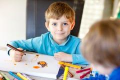 Twee kleine jong geitjejongens die op school een verhaal met kleurrijke pennen schilderen Stock Afbeeldingen