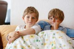 Twee kleine jong geitjejongens die op TV thuis letten Stock Foto