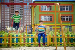 Twee kleine jong geitjejongens die pret met schommeling op openluchtspeelplaats hebben Kinderen, beste vrienden en siblings die o royalty-vrije stock afbeelding