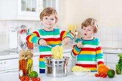 Twee kleine jong geitjejongens die spaghetti in binnenlandse keuken eten Stock Foto