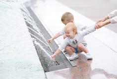 Twee kleine jonge geitjes die in de stads vierkante fontein spelen De kinderen houden brij door een hand stock afbeelding
