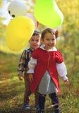 Twee kleine jonge geitjes die met ballons in het park spelen Royalty-vrije Stock Afbeeldingen